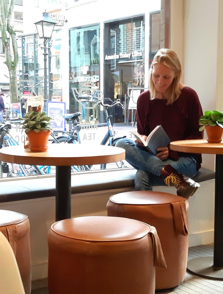 Marjolijn Knippels zit binnen bij de Chocolate Company op de vensterbank met een boek in haar hand rustig te lezen.
