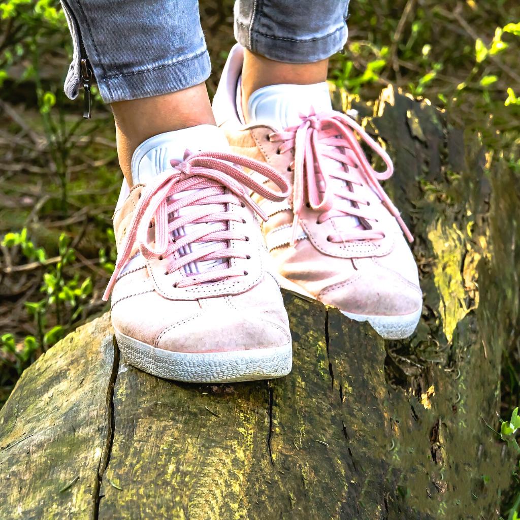Een vrouw die over een boomstam loop in het bos. Ze heeft licht rose gympen aan.