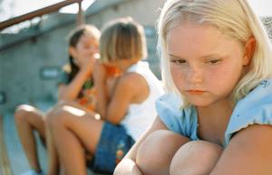 3 kleinere kinderen waarvan er 2 met elkaar kletsen en de derde niet mee mag doen. Zij kijkt verdrietig van zich weg en heeft zich terug getrokken