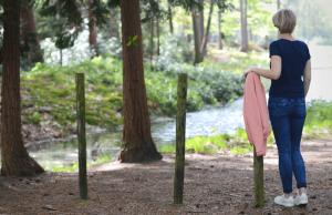 ikzelf, marjolijn knippels. leunend op een paaltje in een bos. ik kijk voor me uit, maar sta met mijn rug richting te fotograaf en de zon schijnt in de verte