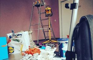 een foto van mijn nieuwe werkruimte die ik aan het opknappen ben. Er staan verfspullen, bouwlamp, trap, stofzuiger en een hoop afval