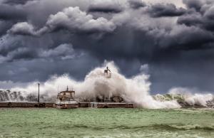 een spectaculaire foto van storm bij een zee waarin je goed verschil ziet tussen de lucht en de zee. Een hoge golf die de vuurtoren helemaal bedekt en een bootje dat nog aan een steiger ligt