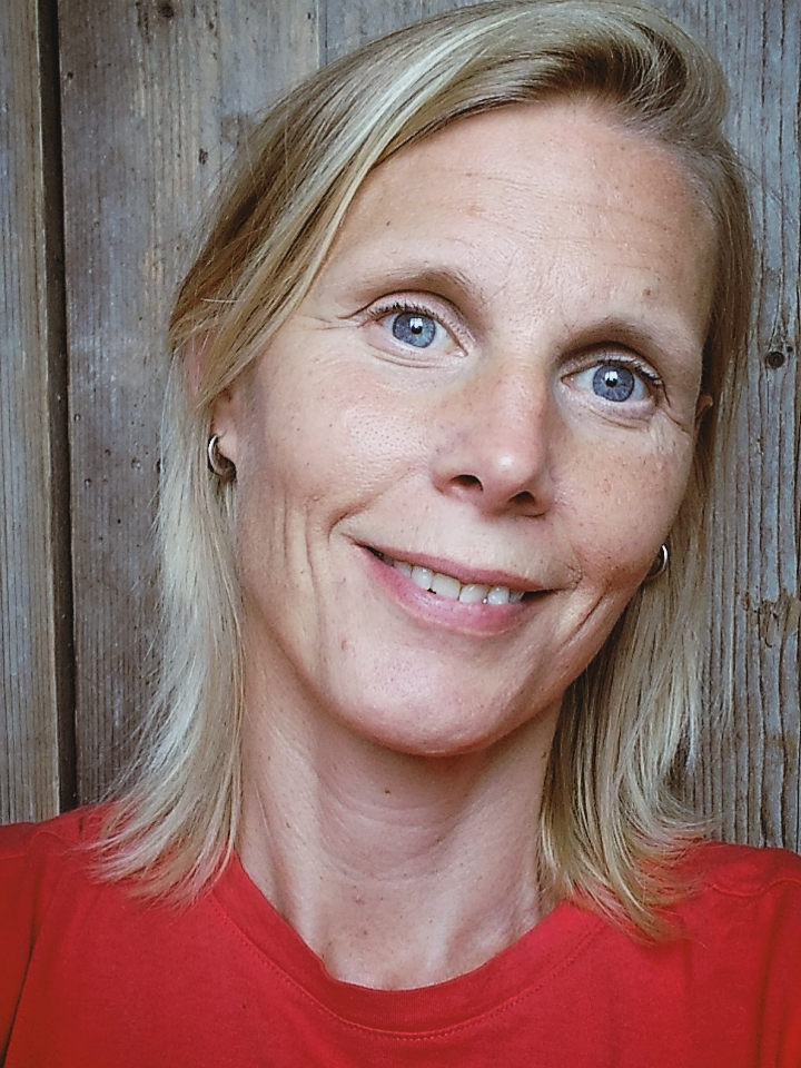 Profielfoto van Marjolijn Knippels waarop ze in een rood t-shirt is gekleed en half lange blonde haren heeft