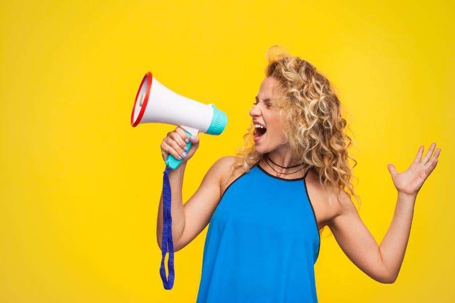 vrouw roept door megafoon op gele achtergrond en blauw topje