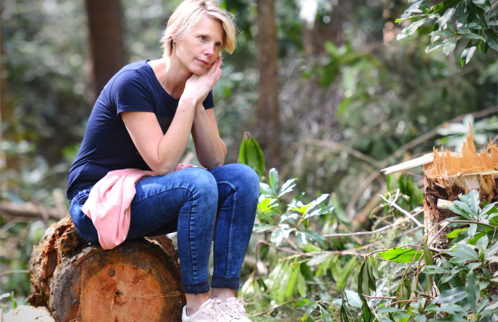 Marjolijn Knippels zittend op boomstammen in het bos